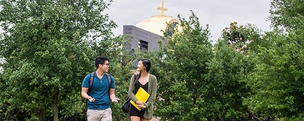 Two University of St. Thomas – Houston students walk in front of Chapel of St. Basil